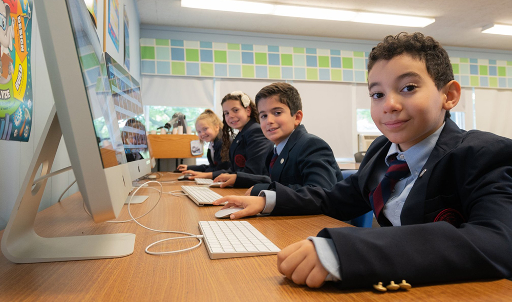 Students learning on computers at the best private school in the capital district